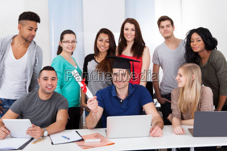 college student holding degree with classmates
