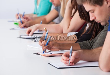 university students writing at desk