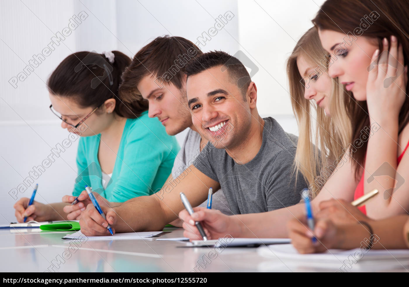 handsome, student, sitting, with, classmates, writing - 12555720