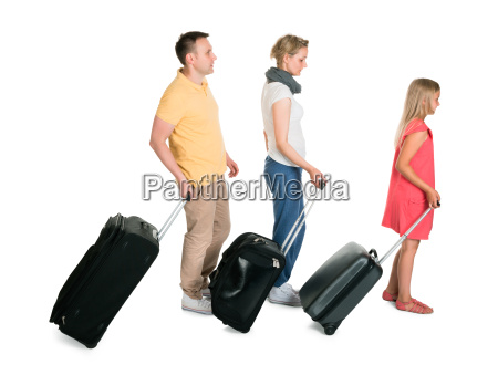 young family walking with luggage
