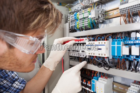 electrical engineer examining fusebox with multimeter