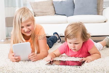 kids, using, tablet, lying, on, carpet - 12556168
