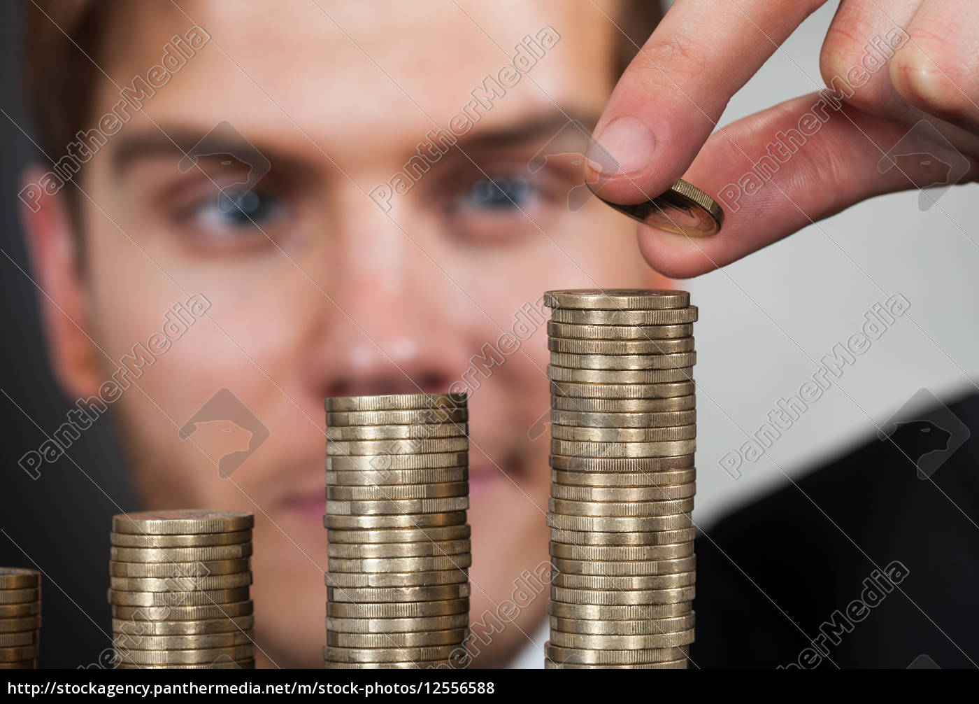 young, businessman, stacking, coins, at, desk - 12556588