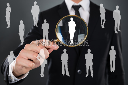 businessman searching candidate with magnifier