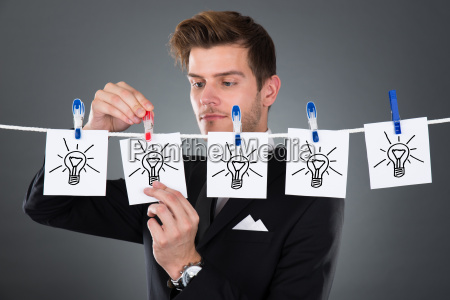 businessman pinning papers lightbulbs on clothesline