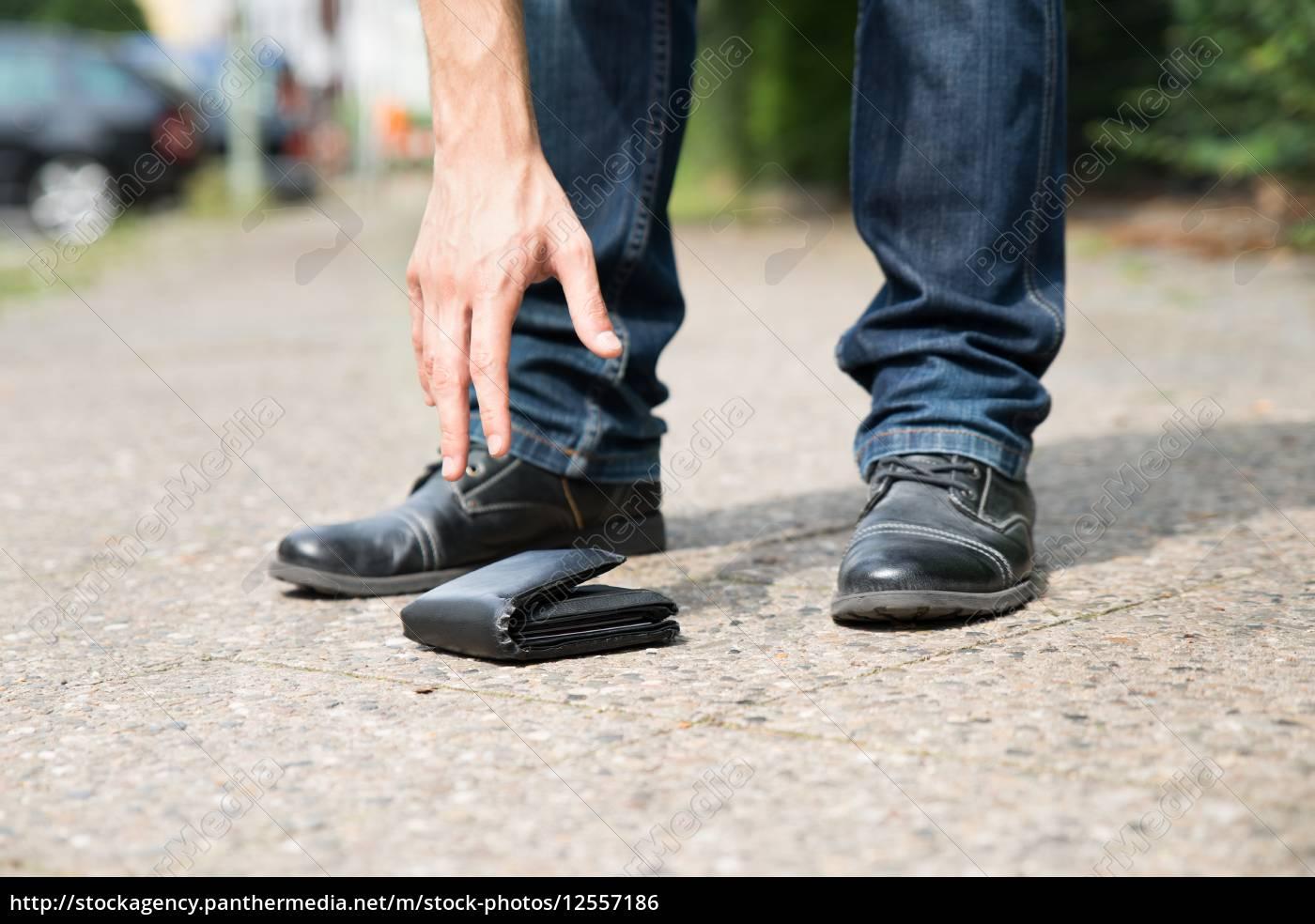 man, picking, up, fallen, wallet - 12557186