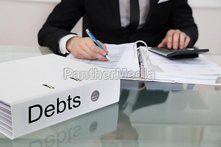 businessman calculating debts at desk
