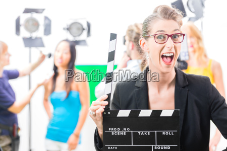 woman with clapperboard in production on