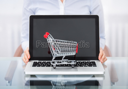 businessperson, with, shopping, cart, and, laptop - 12558096
