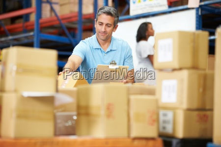 workers in warehouse preparing goods for