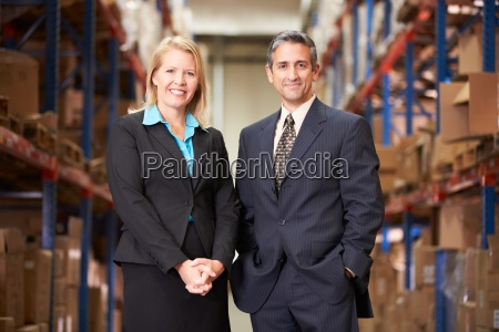 businesswoman, and, businessman, in, distribution, warehouse - 12564366