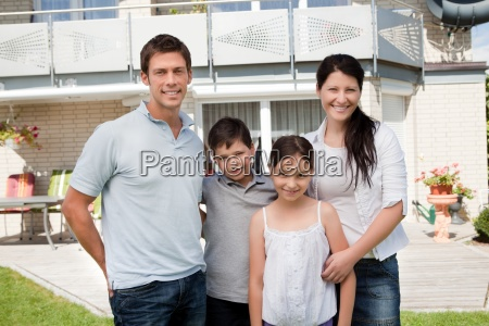 caucasian family outside their new house