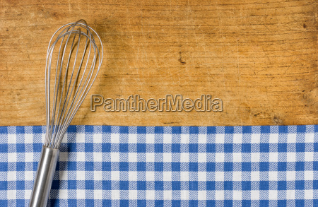 whisk on wooden background with blue