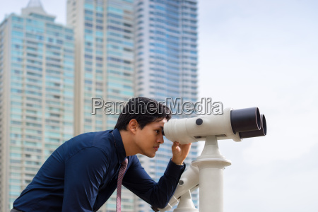 asian business man with binoculars looking