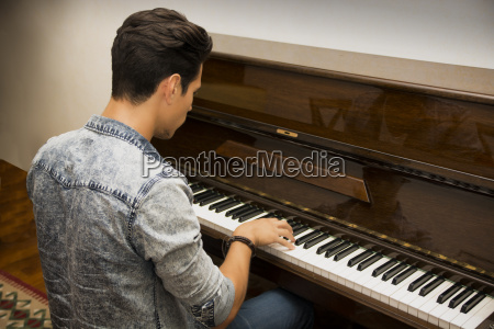 young handsome male artist playing classical