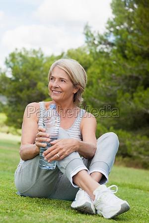 happy mature woman in sportswear drinking