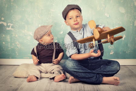 two brothers playing with wooden flyers