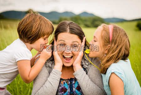 children blowing whistle to mothers ears