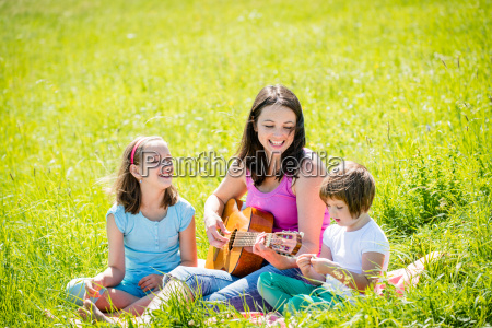 mother playing guitar in nature to