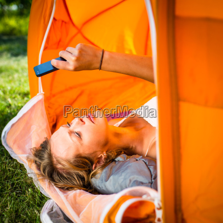 pretty young woman camping outdoors lying