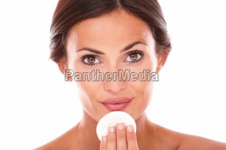 hispanic woman applying facial care product