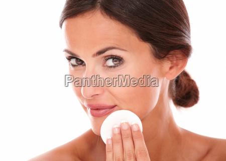 latin woman applying moisturizer on her