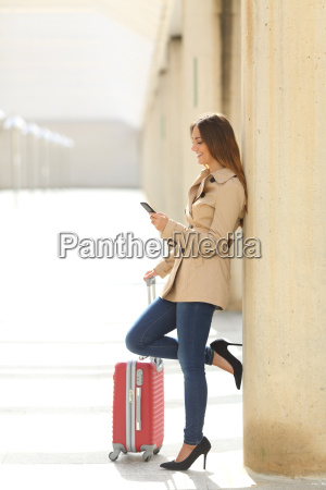 traveler woman texting a smartphone while