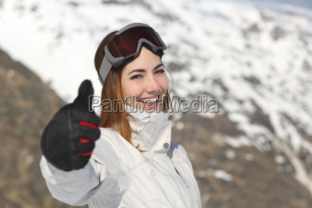 positive skier woman gesturing thumb up