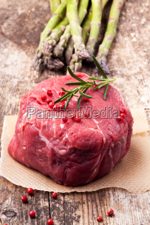 raw steak with asparagus on wood