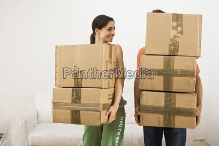 couple moving house carrying stack of