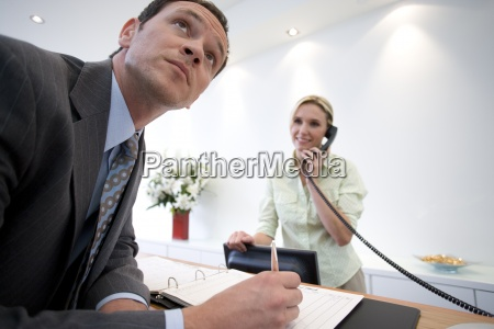 businessman signing at reception by receptionist