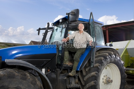 farmer leaning out of tractor