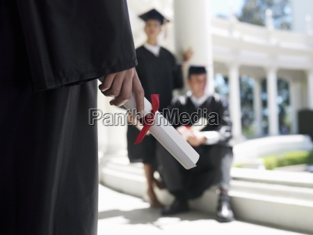 university student in graduation gown holding