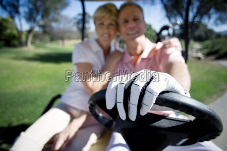 mature couple sitting in golf buggy