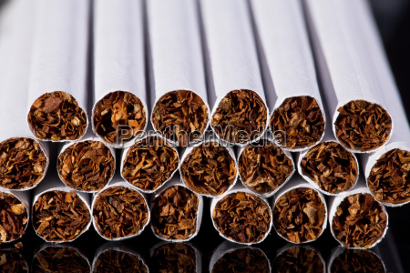 some thin cigarettes on black background