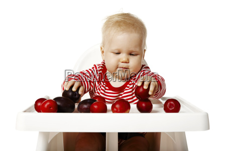 baby is selecting plums