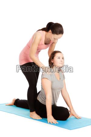 yogalehrerin gibt hilfestellung beim training eka