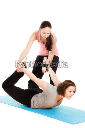 yogalehrerin gibt hilfestellung beim training dhanurasana