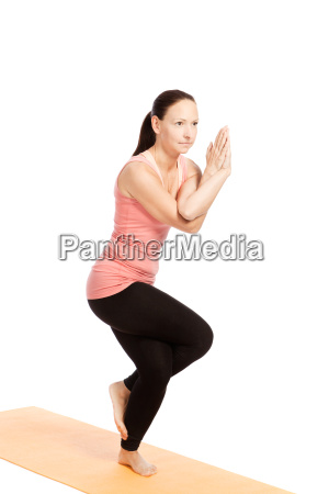 yoga posture garudasana against a white