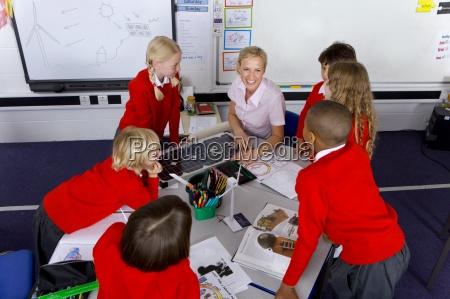 teacher and school children looking at