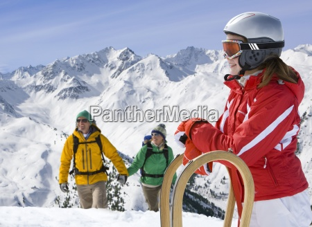 girl standing in snow with sled