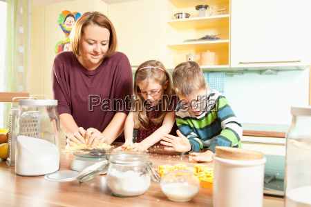 mother bakes cookies with her children