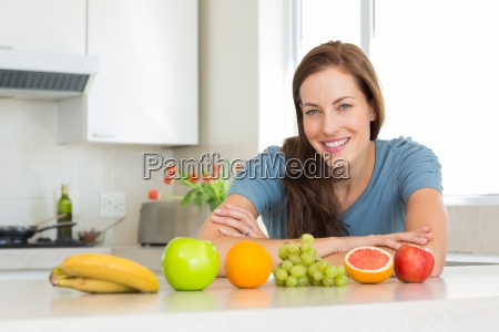 smiling woman with fruits on kitchen