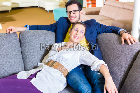 couple buying couch in furniture shop
