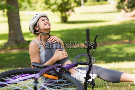 female bicyclist with hurt leg sitting