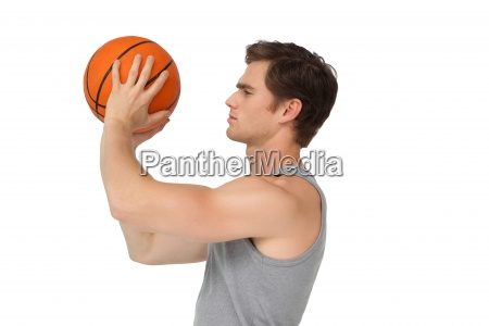 athletic man holding basketball about to