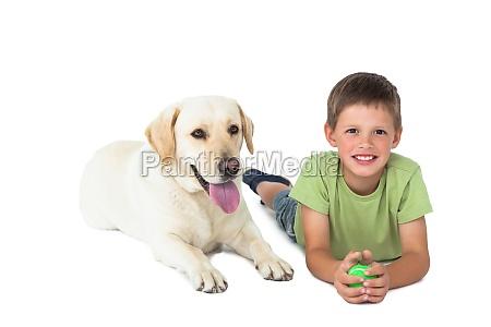 cute little boy holding ball lying