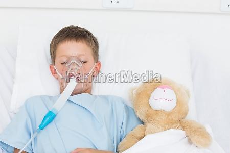 boy wearing oxygen mask sleeping beside
