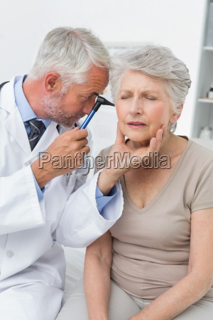 male doctor examining senior patients ear