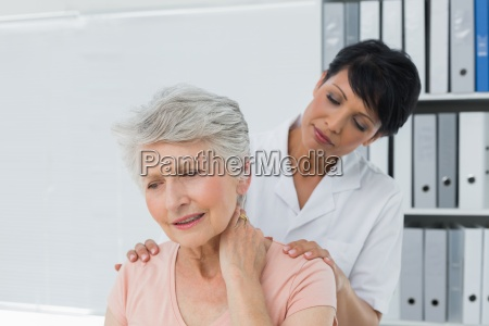 chiropractor looking at senior woman with
